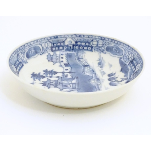 36 - A Chinese blue and white dish / bowl with hand painted decoration depicting a landscape with trees, ...