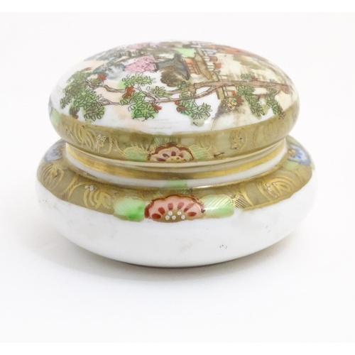 40 - A Japanese Noritake circular pot and cover with hand painted decoration depicting a Geisha girl in a...