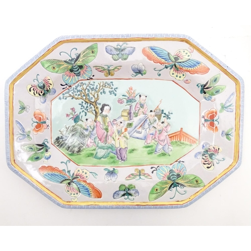 49 - A Japanese charger with hand painted decoration depicting Geisha girls in a garden with a floral bor...