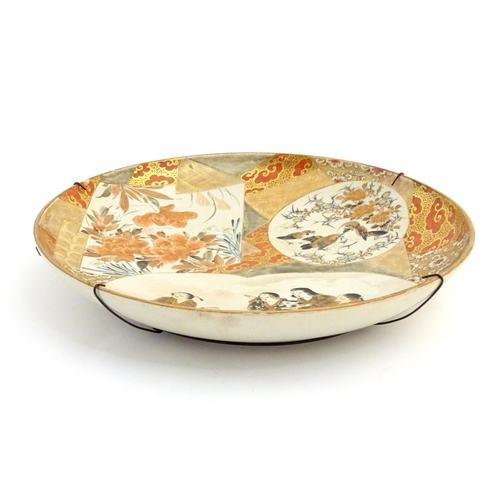 50 - A Japanese satsuma charger with hand painted panelled decoration depicting stylised peony flowers, a...