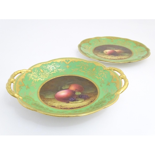 56 - A Coalport twin handled dish and plate with a green and gilt ground with hand painted central fruit ...
