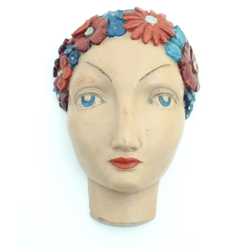 58 - An Art Deco plaster wall mask, formed of the head of a woman with a floral headdress in the manner o...
