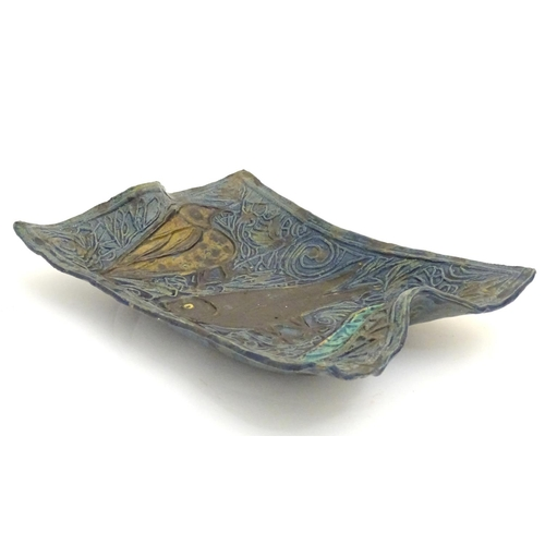 59 - A Scandinavian studio pottery shaped dish with relief decoration depicting three birds. Indistinct m...