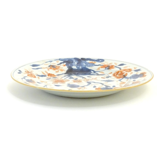9 - A Japanese plate in the Imari palette with hand painted decoration depicting blossoming flowers. App...