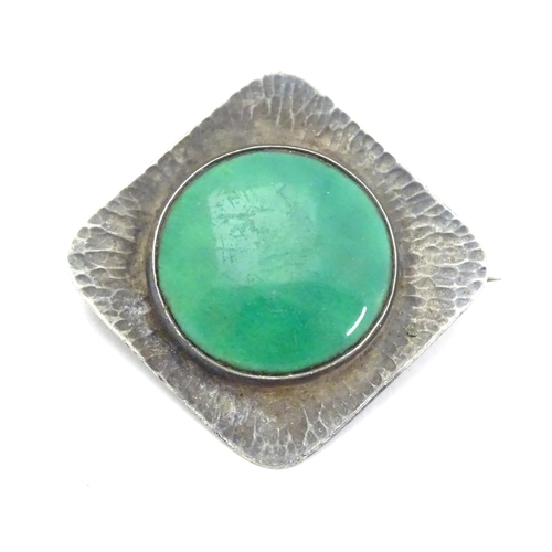 """An Arts & Crafts brooch set with green Ruskin style cabochon within a textured silver mount, marked sterling silver to reverse. Approx. 1 1/2"""" wide."""