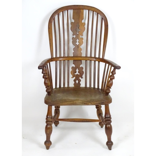 """An early 19thC yew wood double bow back Windsor chair, having a pierced back splat flanked by shaped armrests and an elm seat, the chair raised on turned tapering legs united by a H-stretcher. 25"""" wide x 17"""" deep x 41"""" high."""