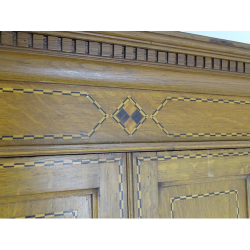 1321 - An early / mid 20thC oak triple wardrobe, having a moulded dentil carved cornice above a checkered i...