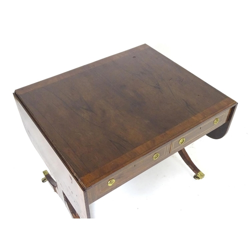 1322 - A Georgian rosewood sofa table with a rectangular crossbanded top flanked by two drop leaves, The ta...