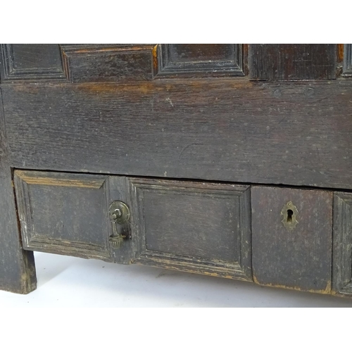 1324 - A late 17thC oak mule chest with a moulded lifting lid above a panelled front having geometric mould...