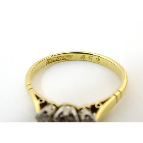553A - An 18ct gold ring set with a trio of platinum set diamonds to top. Ring size approx. size K...