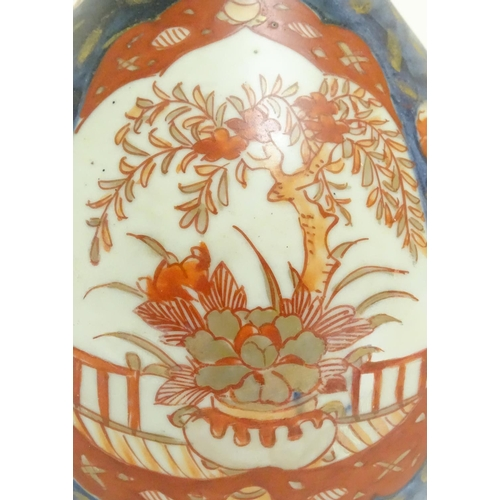 13 - An Oriental double gourd vase in the Imari palette with lobed panels depicting plants on a terrace, ...
