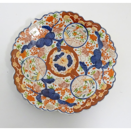 17 - A Japanese Imari plate with a scalloped rim with stylised leaf veins in relief to the centre, decora...