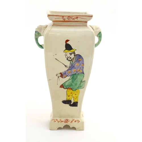 22 - An Oriental vase with twin handles of elephant head form. The body with hand painted figures and fol...