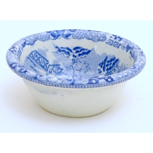 24 - A 19thC blue and white small strainer, decorated with an Oriental landscape scene with pagodas etc. ...
