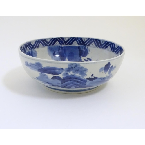 46 - A Chinese blue and white bowl with hand painted decoration depicting an Oriental landscape with pago...