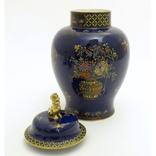 120 - A Wiltshaw and Robinson Carlton Ware baluster vase and cover decorated with flowers, with a blue gro...