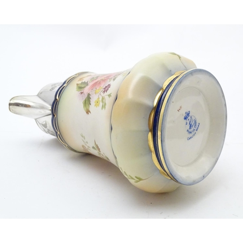121 - A Wiltshaw & Robinson Carlton Ware jug with floral decoration, with silver plate mounts and handle. ...