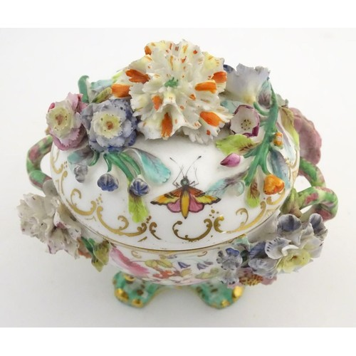 158 - A German twin handled pot and cover on scrolled feet, decorated in relief with encrusted flowers, la...