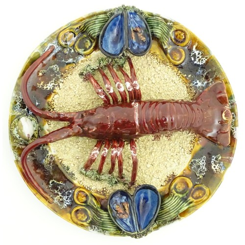 172 - A 20thC Portuguese Palissy style majolica dish with an applied model of a lobster on a bed of sand a...