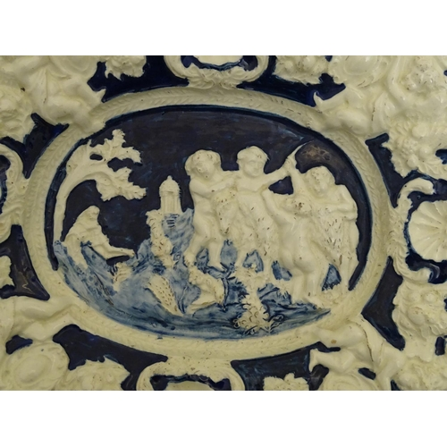 174 - An Italian style charger of oval form with relief decoration depicting putti in a landscape with a g...