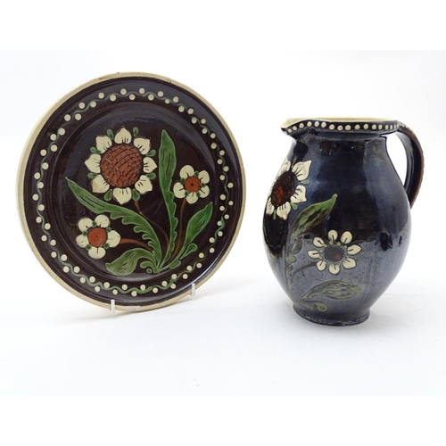 180 - Two items of Continental studio pottery comprising a jug and a plate with floral and foliate detail....