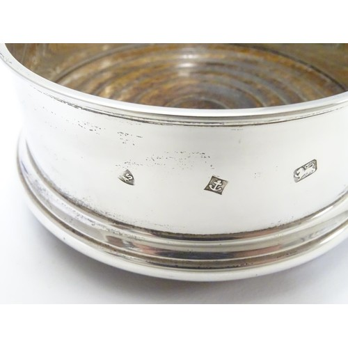 245 - A silver coaster with turned wooden base. Hallmarked Birmingham 1987 maker Argyll Silver. 4