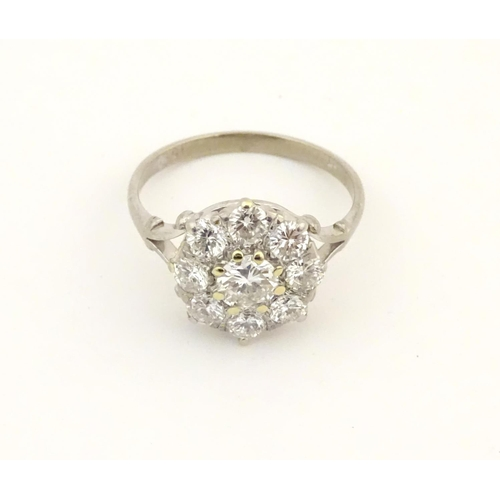520 - An 18ct white gold diamond cluster ring, the central diamond approx. 0.7ct  bordered by 8 brilliant ...