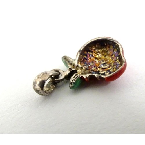 607 - A silver pendant / charm formed as a bitten apple with enamel decoration. ¾'' long
