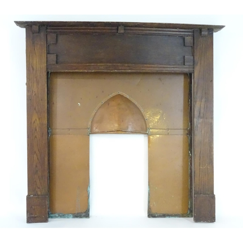 879 - An early 20thC oak and copper fire surround. 56