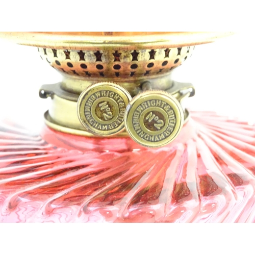 900 - A Victorian oil lamp, the brass column with cranberry glass reservoir and shade. The twin burners ma...