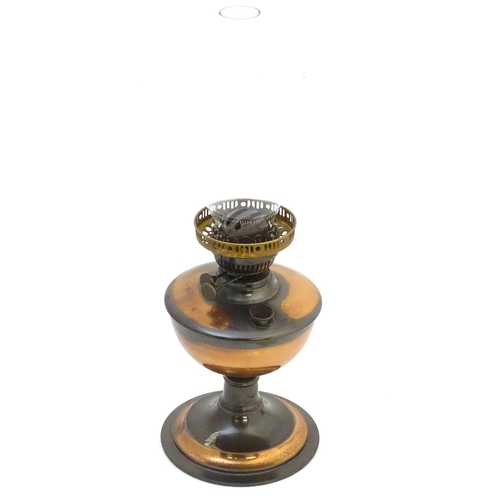 902 - A late 19thC / early 20thC oil lamp with  glass chimney. Approx 19 1/2