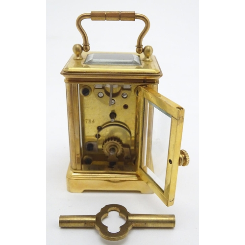 927 - A large 20thC carriage clock of glit metal and bevelled glass construction, with a white enamel dial...