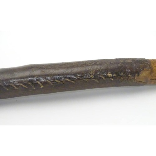 947 - Ethnographic / Native / Tribal: A club with a leather bound handle and metal end. Approx. 22 1/4