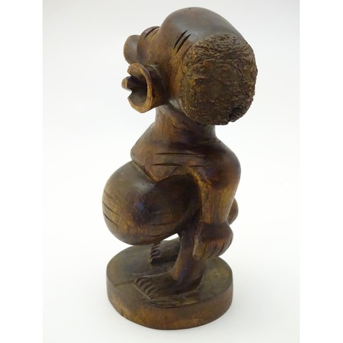 954 - Ethnographic / Native / Tribal: A carved wooden native figure on a circular base. Approx. 8 1/2