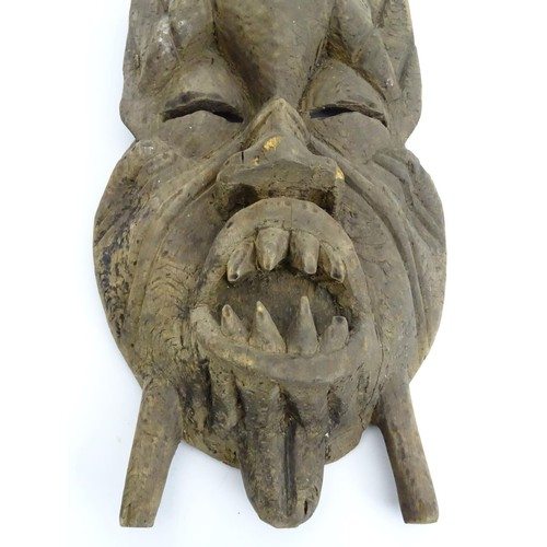 959 - Ethnographic / Native / Tribal: A West African mask with bared teeth. Approx. 27