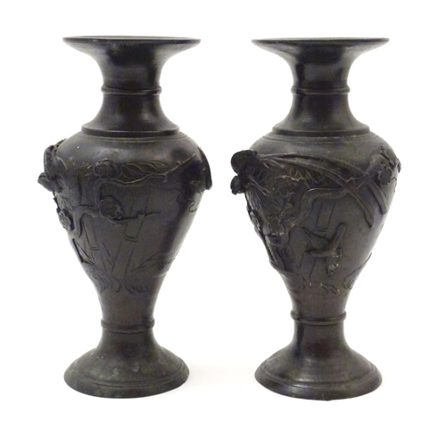 1011 - A pair of Japanese cast metal vases decorated with birds amongst trees and foliage in relief. Maker'...