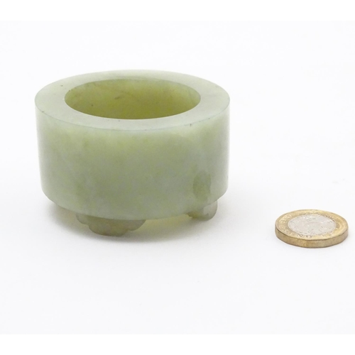 1012 - A small Chinese jade brush pot of cylindrical form raised on four feet. Approx. 1 1/2