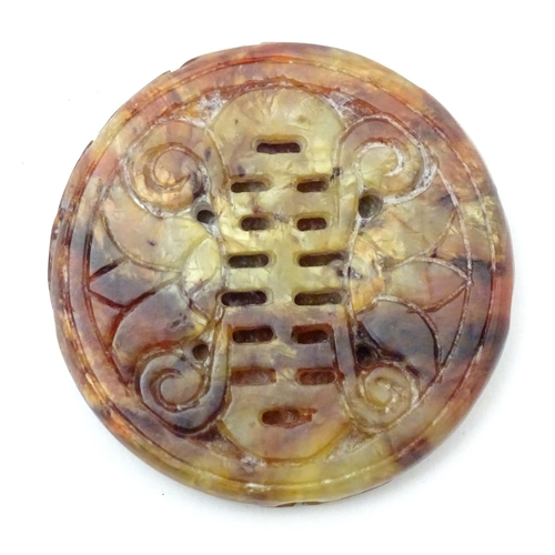 1027 - An Oriental hardstone roundel carving depicting stylised foliage and birds. Approx. 2 1/4