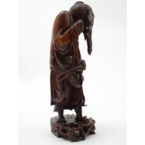 1038 - A Chinese carved wooden figure depicting a sage / elder. Approx. 11 1/2