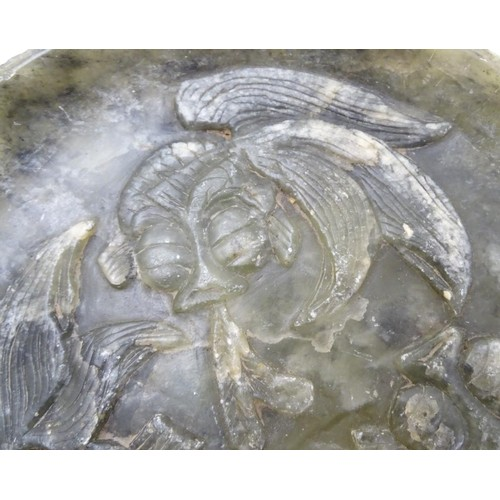1050 - An Oriental carved soapstone plate depicting three carp / koi fish in relief. Approx. 7 1/8