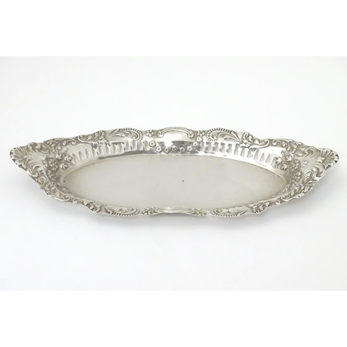 252 - A silver dish of oval form with pierced and embossed decoration , hallmarked Birmingham 1899 maker J...