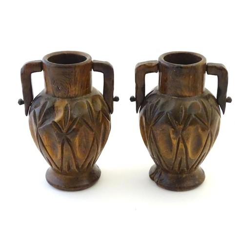 1106 - A pair of late 19th / early 20thC treen carved and turned vases with twin handles, dimple decoration...