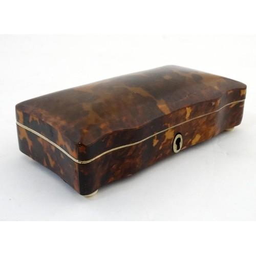 1107 - A 19thC tortoiseshell box with velvet lining and squat bun feet. 1 3/4