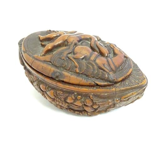 1120 - A Continental carved nut snuff box, the hinged lid decorated with a horse and a man carrying a woman...