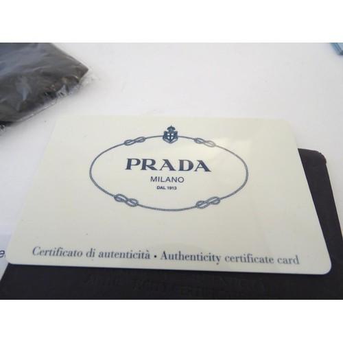 1128 - A pair of Prada sunglasses with original case, box, card of authenticity etc.