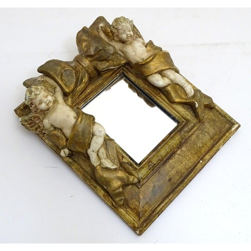 1208 - A contemporary wall mirror with gilt and cream decoration of cherubs flanking a bow, the whole 9 1/3...