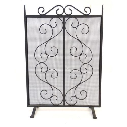 1242 - A 20thC wrought iron spark guard / fire screen with scrolling detail. Together with a small companio...
