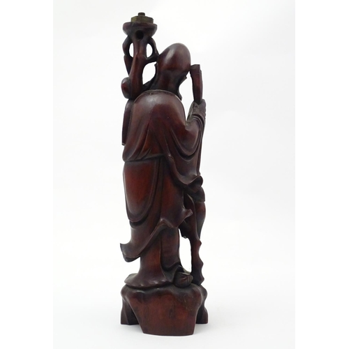 1247 - A 20thC Chinese carved wooden figure modelled as an elder with a scroll and crane bird. Approx. 20