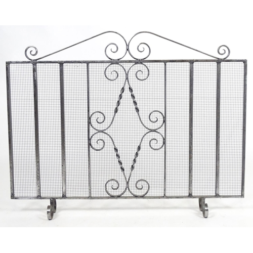 1270 - A 20thC wrought iron spark guard / fire screen with scrolling detail. Together with a small companio...