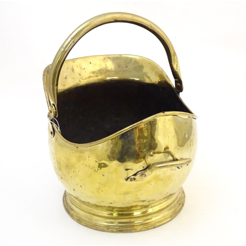 1281 - A late 19th / early 20thC brass coal scuttle of helmet form with a swing handle and small rear handl...